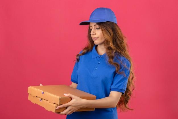 Jovem entregadora com cabelo encaracolado, vestindo uma camisa pólo azul e boné em pé com caixas de pizza com o rosto infeliz, parecendo triste sobre um fundo rosa isolado