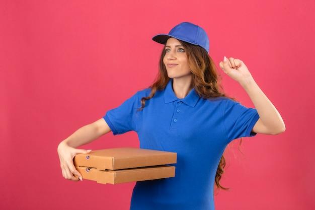 Jovem entregadora com cabelo encaracolado, vestindo uma camisa pólo azul e boné em pé com caixas de pizza levantando o punho após um conceito de vencedor de rosto feliz da vitória sobre fundo rosa isolado
