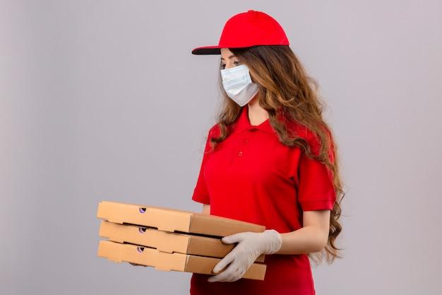 Jovem entregadora com cabelo encaracolado, vestindo uma camisa pólo vermelha e boné com máscara de proteção médica e luvas em pé com caixas de pizza, parecendo muito triste e infeliz sobre um fundo branco isolado