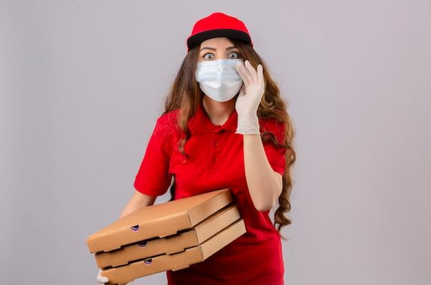 Jovem entregadora com cabelo encaracolado, vestindo uma camisa pólo vermelha e boné com máscara de proteção médica e luvas em pé com caixas de pizza, parecendo surpresa com uma mão perto da boca contando um segredo.