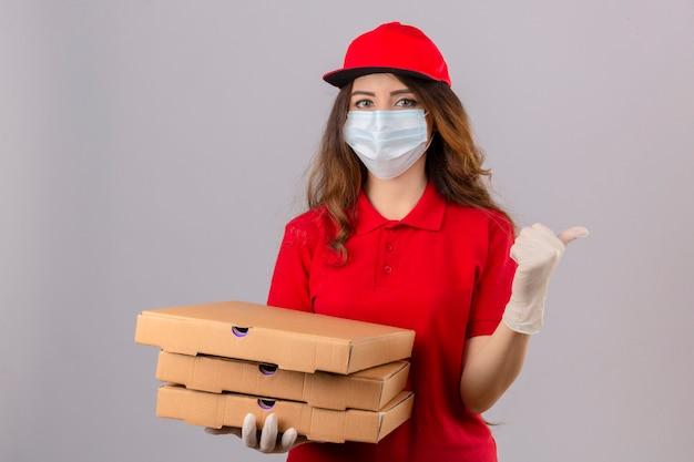 Jovem entregadora com cabelo encaracolado, vestindo uma camisa pólo vermelha e boné com máscara protetora médica e luvas em pé com caixas de pizza apontando e aparecendo com o polegar para o lado com sorriso no rosto feliz