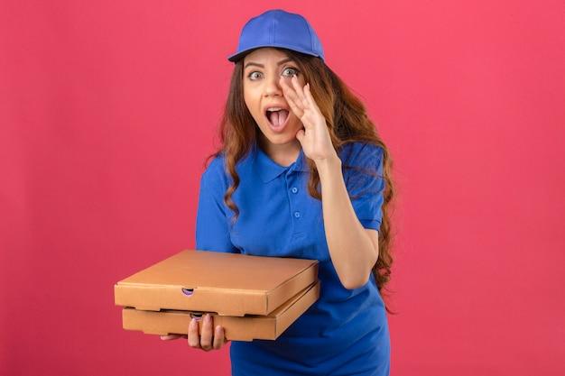 Jovem entregadora de cabelos cacheados, usando uma camisa pólo azul e boné em pé com caixas de pizza gritando com a boca bem aberta sobre um fundo rosa isolado