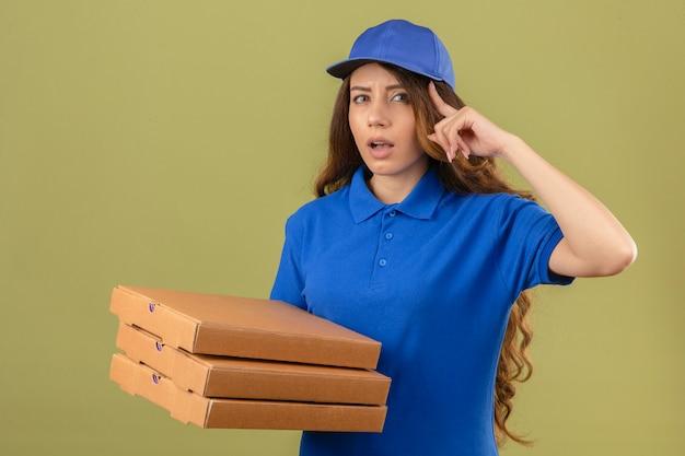 Jovem entregadora de cabelos cacheados, vestindo uma camisa pólo azul e boné com uma pilha de caixas de pizza apontando para o templo com o dedo pensando focado em uma tarefa sobre um fundo verde isolado