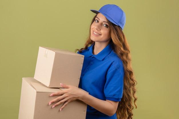 Jovem entregadora de cabelos cacheados, vestindo uma camisa pólo azul e boné em pé com caixas de papelão, sorrindo amigavelmente sobre um fundo verde isolado