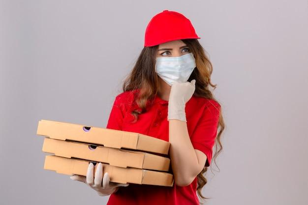 Jovem entregadora de cabelos cacheados, vestindo uma camisa pólo vermelha e boné com máscara protetora médica e luvas em pé com caixas de pizza pensando concentrado na dúvida com a mão no queixo sobre o isolado