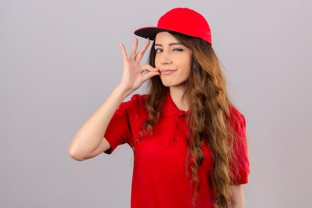 Jovem entregadora de cabelos cacheados, vestindo uma camisa pólo vermelha e boné, fazendo gesto de silêncio e fechando a boca com um zíper sobre fundo branco isolado