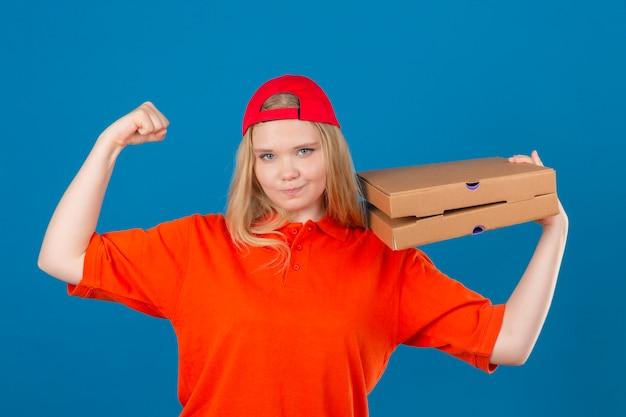 Jovem entregadora de camisa pólo laranja e boné vermelho em pé com caixas de pizza no ombro levantando o punho como uma vencedora sobre fundo azul isolado