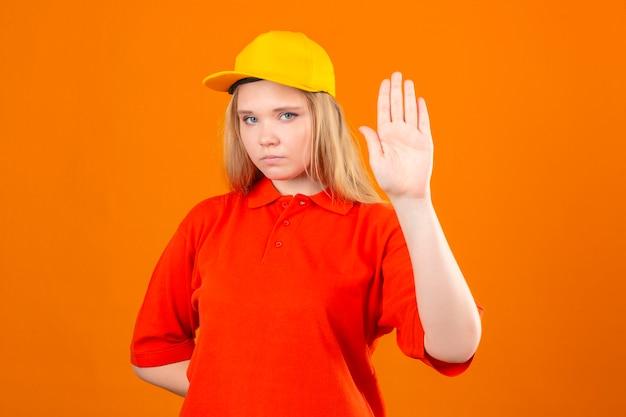 Jovem entregadora de camisa pólo vermelha e boné amarelo em pé com a mão aberta, fazendo sinal de pare com gesto de defesa de expressão sério e confiante sobre fundo laranja isolado