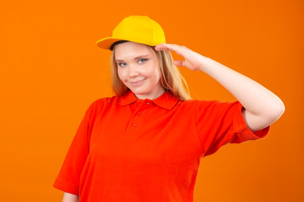 Jovem entregadora de camisa pólo vermelha e boné amarelo saudando, parecendo confiante sobre um fundo laranja isolado