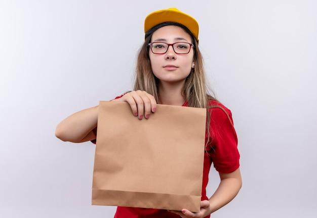 Jovem entregadora de camisa pólo vermelha e boné amarelo segurando um pacote de papel, olhando para a câmera com uma expressão séria e confiante