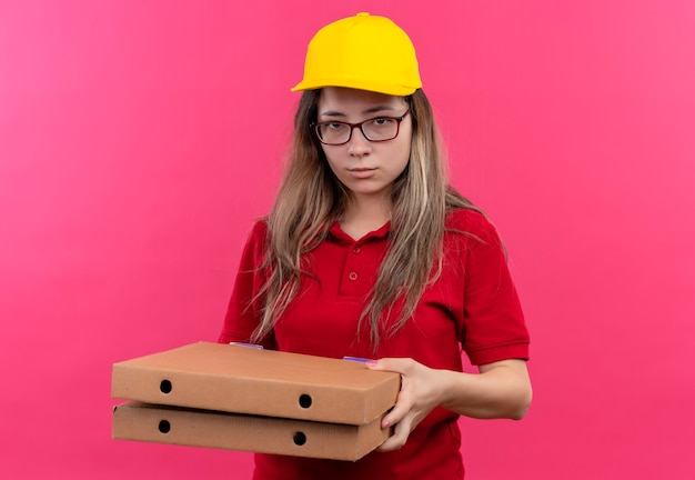 Jovem entregadora de camisa pólo vermelha e boné amarelo segurando uma pilha de caixas de pizza olhando para a câmera com uma expressão triste no rosto