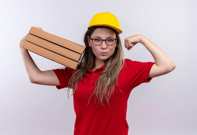 Jovem entregadora de camisa pólo vermelha e boné amarelo segurando uma pilha de caixas de pizza, posando como uma vencedora, mostrando bíceps sorrindo confiante