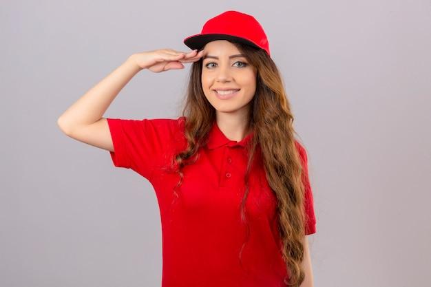 Jovem entregadora de camisa pólo vermelha e boné saudando olhando para a câmera, sorrindo amigavelmente sobre fundo branco isolado