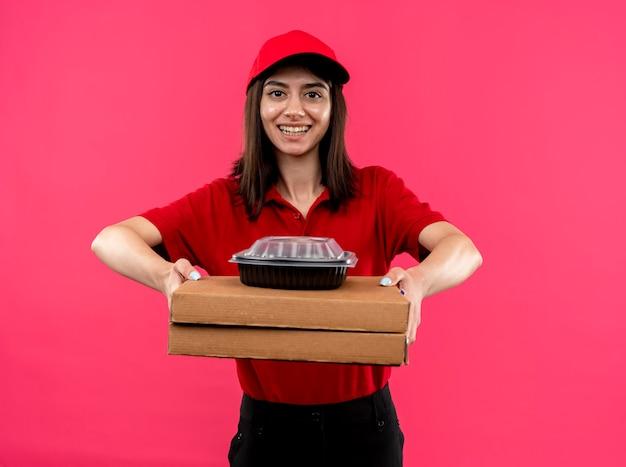 Jovem entregadora de camisa pólo vermelha e boné segurando caixas de pizza e um pacote de comida, olhando para a câmera, sorrindo com uma cara feliz em pé sobre um fundo rosa