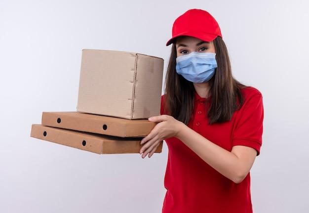 Jovem entregadora de camiseta vermelha com boné vermelho e máscara, segurando uma caixa e uma caixa de pizza no fundo branco isolado