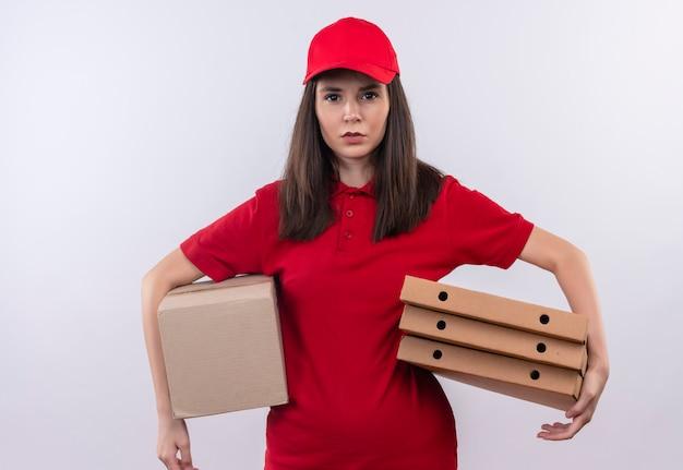 Jovem entregadora de camiseta vermelha com boné vermelho segurando uma caixa e uma caixa de pizza no fundo branco isolado