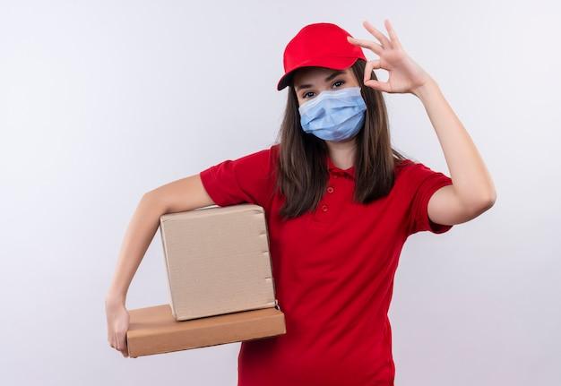 Jovem entregadora de camiseta vermelha com boné vermelho usa máscara segurando uma caixa e uma caixa de pizza mostra um gesto de aprovação em um fundo branco isolado