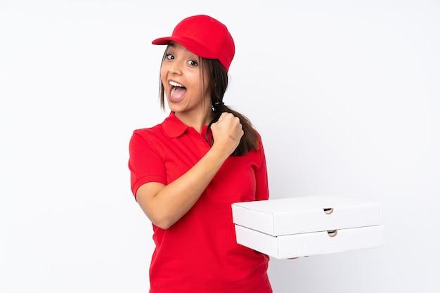 Jovem entregadora de pizza em parede branca isolada comemorando vitória
