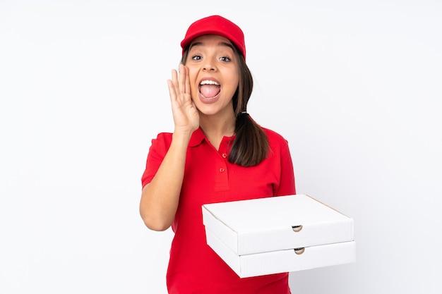 Jovem entregadora de pizza em um fundo branco isolado gritando com a boca bem aberta