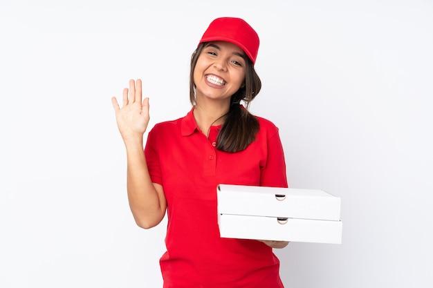 Jovem entregadora de pizza em uma parede branca isolada saudando com a mão com uma expressão feliz