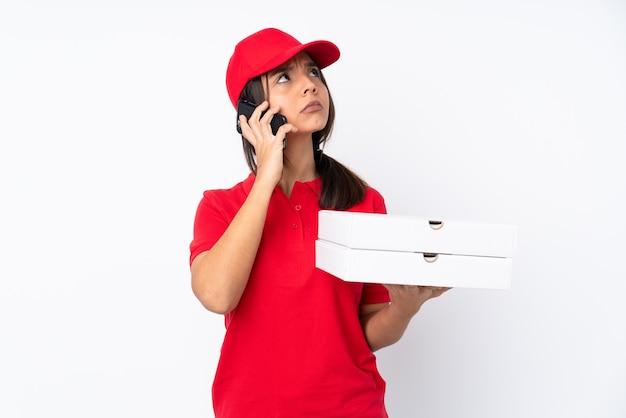 Jovem entregadora de pizza em uma parede branca isolada segurando um café para levar e um celular