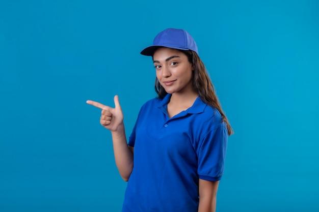 Jovem entregadora de uniforme azul e boné apontando com o dedo para o lado, sorrindo, confiante, feliz e positiva em pé sobre o fundo azul