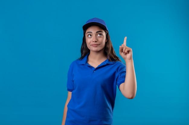 Jovem entregadora de uniforme azul e boné apontando o dedo para cima, concentrada em uma tarefa em pé sobre um fundo azul