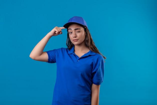 Jovem entregadora de uniforme azul e boné apontando para o templo piscando e olhando para a câmera com expressão confiante focada na tarefa em pé sobre o fundo azul