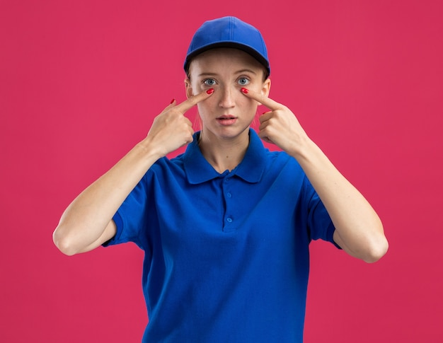 Jovem entregadora de uniforme azul e boné com cara séria apontando com o dedo indicador para os olhos em pé sobre a parede rosa