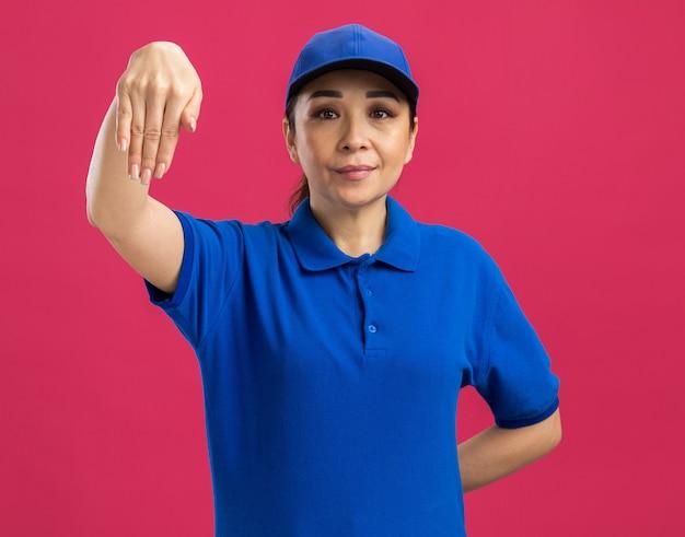 Jovem entregadora de uniforme azul e boné com expressão confiante gesticulando com a mão em pé sobre a parede rosa