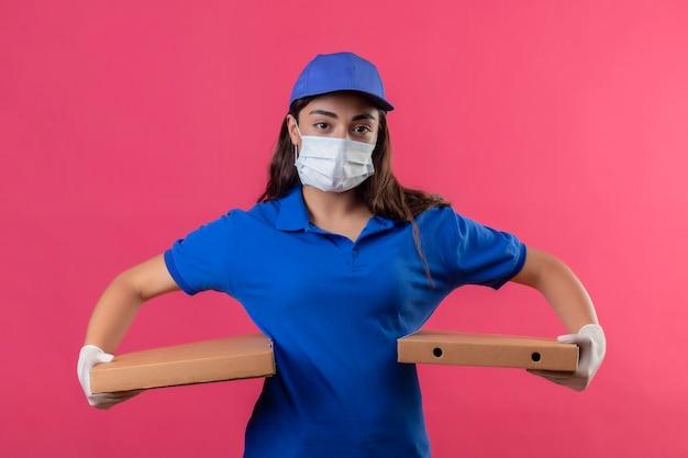 Jovem entregadora de uniforme azul e boné com máscara protetora facial e luvas segurando caixas de pizza, olhando para a câmera com expressão facial séria e confiante em pé sobre o background rosa