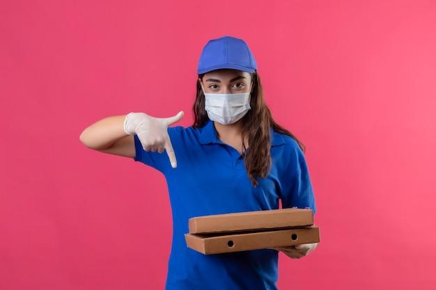 Jovem entregadora de uniforme azul e boné com máscara protetora facial segurando caixas de pizza apontando com o dedo para elas, olhando para a câmera com expressão séria e confiante em pé sobre o pino