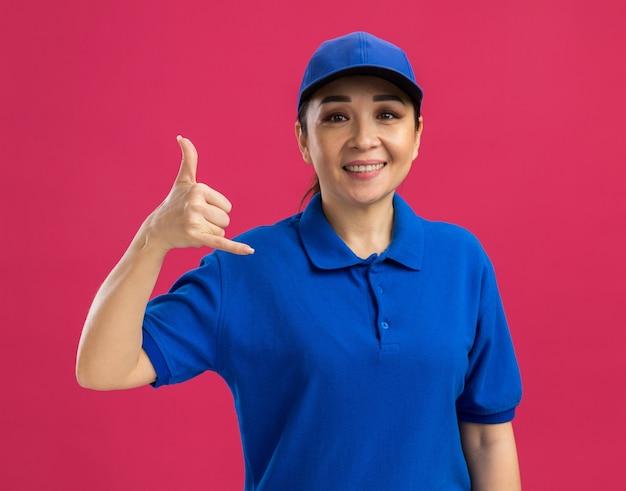 Jovem entregadora de uniforme azul e boné com sorriso no rosto, fazendo gesto de me ligar em pé sobre a parede rosa