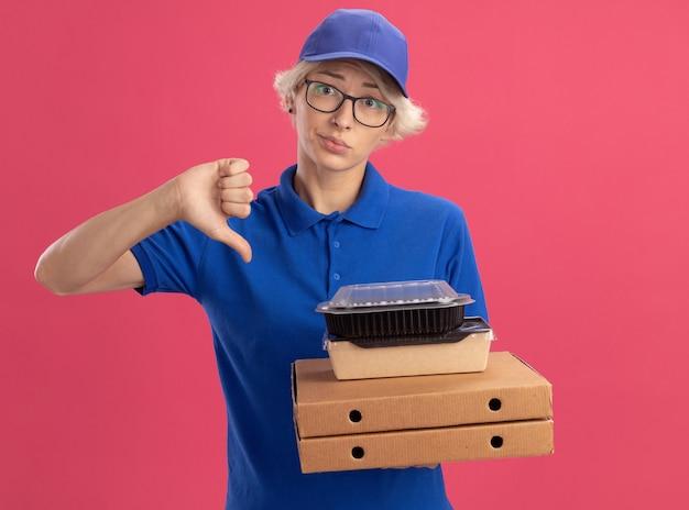 Jovem entregadora de uniforme azul e boné de óculos segurando caixas de pizza e pacotes de comida com uma expressão triste mostrando os polegares para baixo na parede rosa