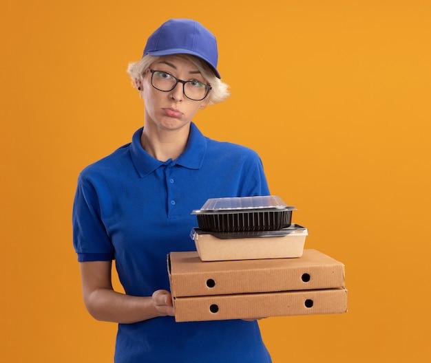 Jovem entregadora de uniforme azul e boné de óculos segurando caixas de pizza e pacotes de comida com uma expressão triste no rosto sobre a parede laranja