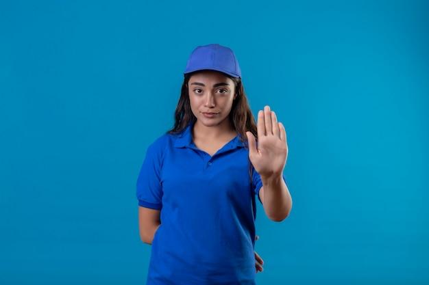 Jovem entregadora de uniforme azul e boné em pé com a mão aberta, fazendo sinal de pare com gesto de defesa de expressão sério e confiante sobre fundo azul