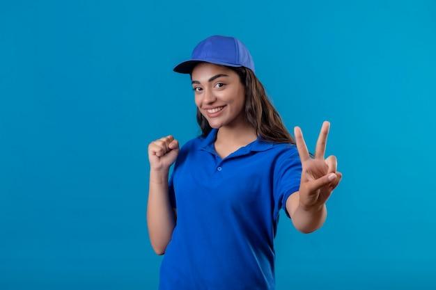Jovem entregadora de uniforme azul e boné em pé com o punho cerrado, mostrando o sinal da vitória ou número dois, sorrindo alegremente feliz e positiva em pé sobre o fundo azul