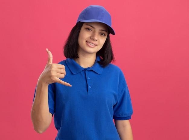 Jovem entregadora de uniforme azul e boné fazendo gesto de me ligar sorrindo em pé sobre a parede rosa