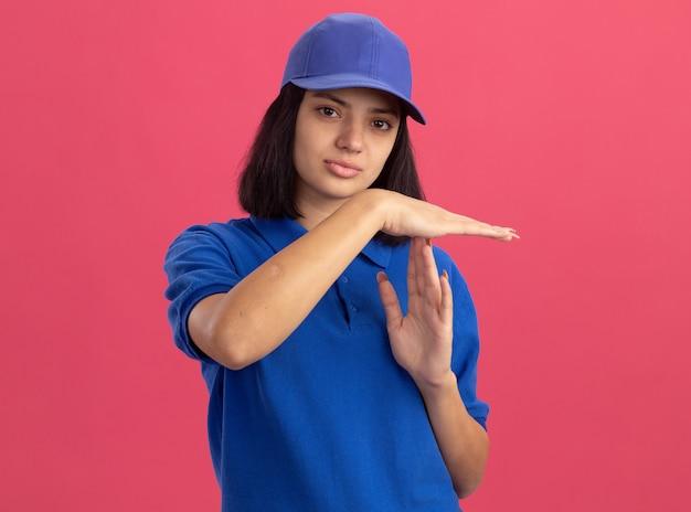 Jovem entregadora de uniforme azul e boné fazendo gesto de pausa com as mãos olhando com uma cara séria em pé sobre a parede rosa