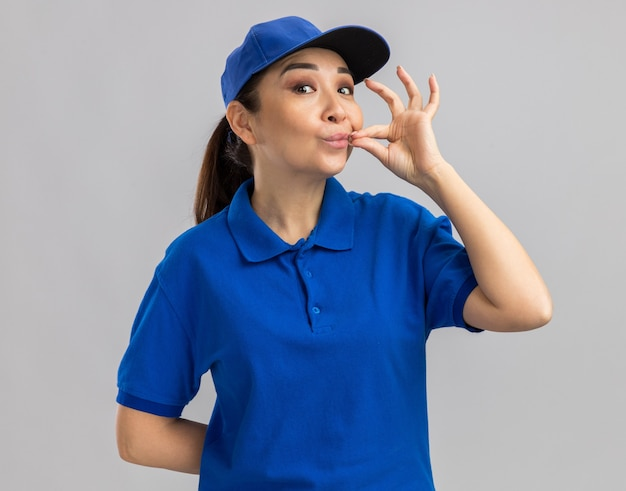 Jovem entregadora de uniforme azul e boné fazendo gesto de silêncio, como fechar a boca com um zíper em pé sobre uma parede branca