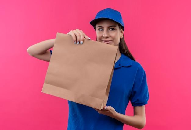 Jovem entregadora de uniforme azul e boné mostrando pacote de papel olhando de lado e sorrindo amigavelmente