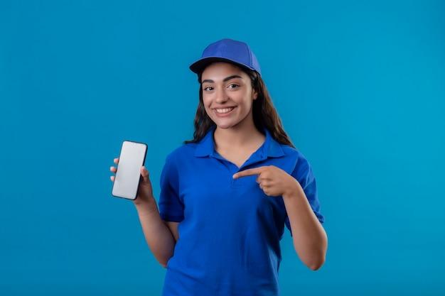 Jovem entregadora de uniforme azul e boné mostrando smartphone apontando com o dedo para ele e sorrindo amigável em pé sobre fundo azul