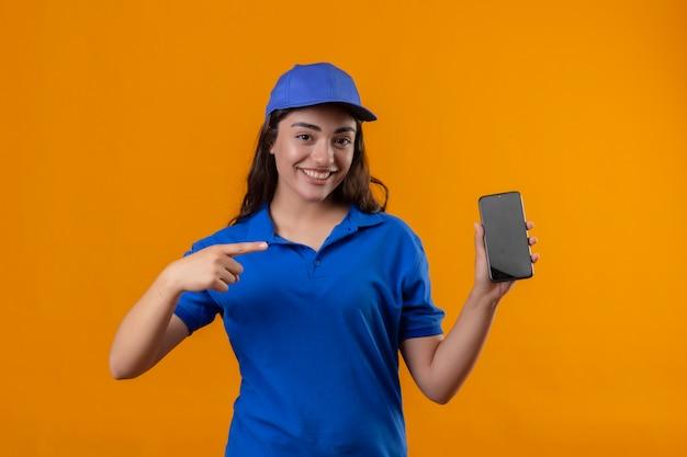 Jovem entregadora de uniforme azul e boné mostrando smartphone apontando com o dedo para ele, sorrindo confiante, olhando para a câmera em pé sobre fundo amarelo