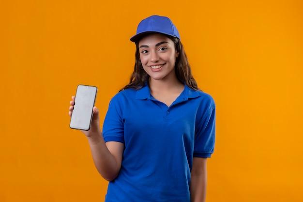Jovem entregadora de uniforme azul e boné mostrando smartphone sorrindo alegremente em pé sobre fundo amarelo