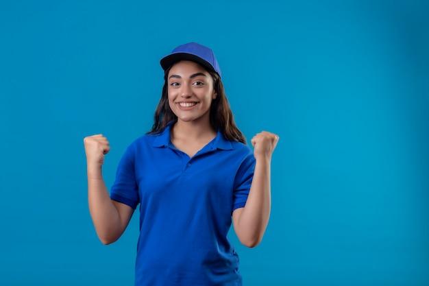 Jovem entregadora de uniforme azul e boné olhando para a câmera, sorrindo alegremente, levantando o punho e comemorando seu sucesso e vitória em pé sobre um fundo azul