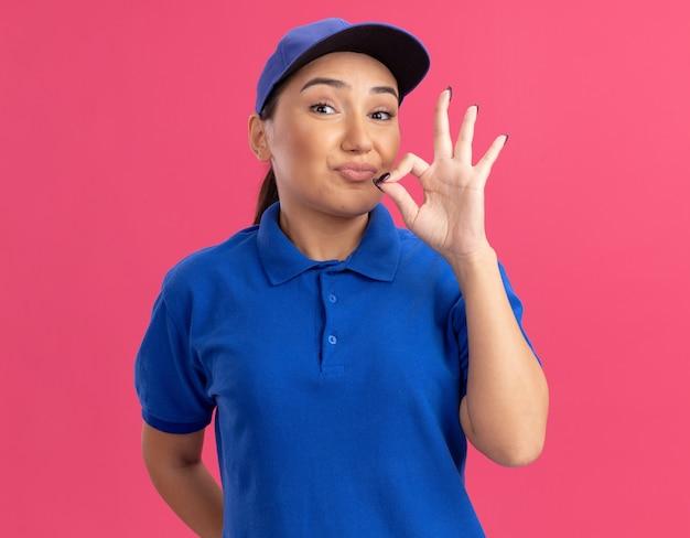 Jovem entregadora de uniforme azul e boné olhando para a frente fazendo gesto de silêncio com os dedos, como fechar a boca com um zíper em pé sobre a parede rosa