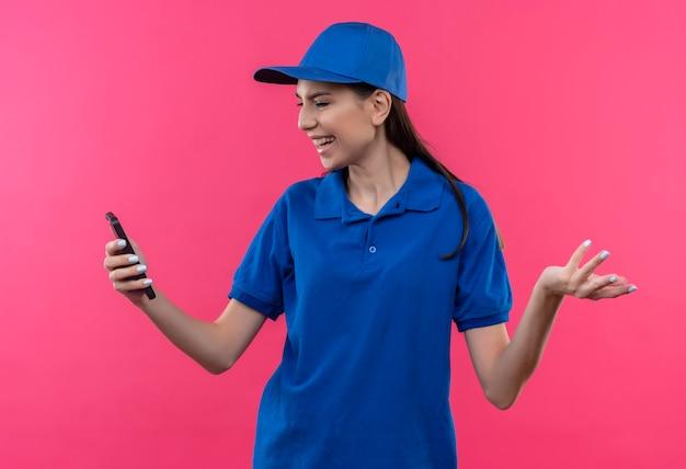 Jovem entregadora de uniforme azul e boné olhando para a tela do smartphone decepcionada
