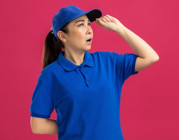 Jovem entregadora de uniforme azul e boné olhando para o lado com expressão pensativa e pensando em pé sobre a parede rosa