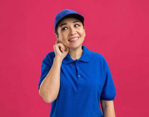 Jovem entregadora de uniforme azul e boné olhando para o lado sorrindo confiante