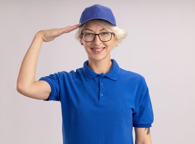 Jovem entregadora de uniforme azul e boné olhando sorrindo alegremente e saudando em pé sobre uma parede branca